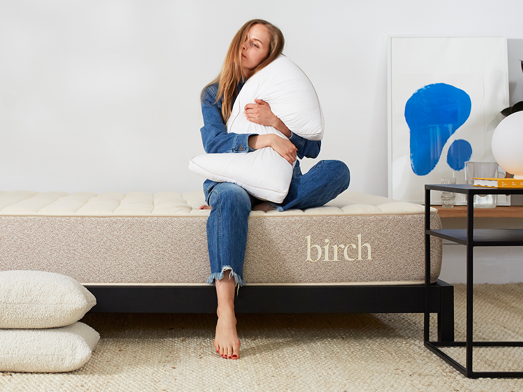 Woman holding a pillow on a Birch Mattress